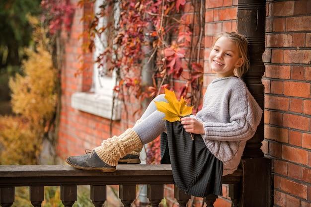 Meisje in een warme trui zit op een houten hek van de veranda van een oud huisje met een vergeeld esdoornblad in haar handen