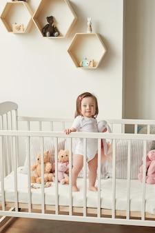 Meisje in een wieg met speelgoed in de kinderkamer