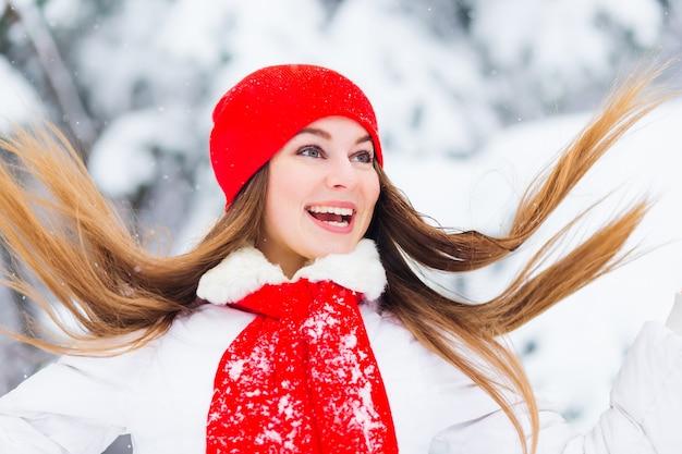 Meisje in een winterjas en een rode hoed met een sjaal die met haar haren zwaait en plezier heeft