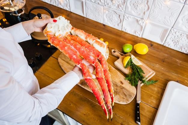 Meisje in een wit jasje met een krab, zeevruchten koken, gezonde voeding, vitamines, keuken