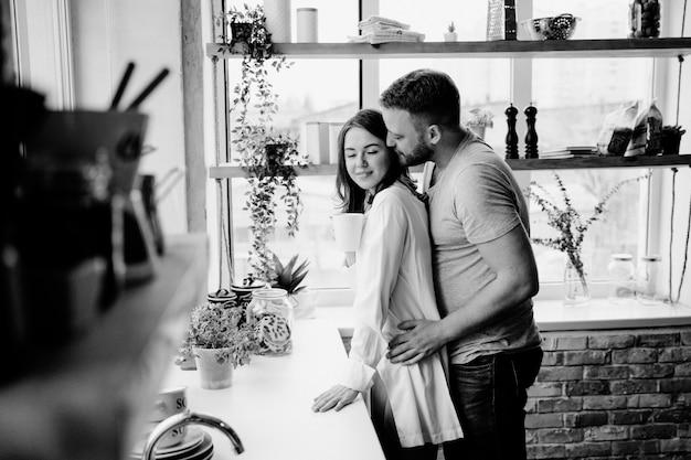 Meisje in een wit overhemd en een kerel in een grijze t-shirt in de keuken. kus en knuffel.