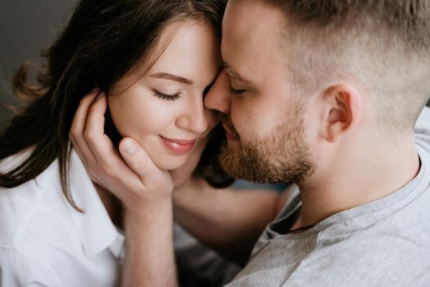 Meisje in een wit overhemd en een man in een grijs t-shirt. kus en knuffel.