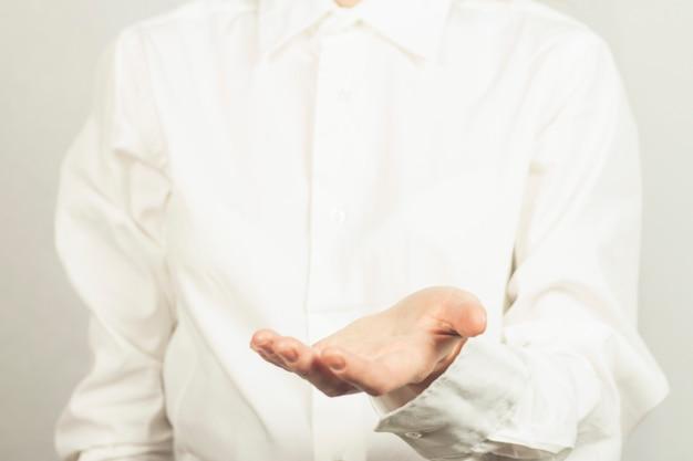 Meisje in een wit shirt houdt voor haar handpalm omhoog. stel cup.