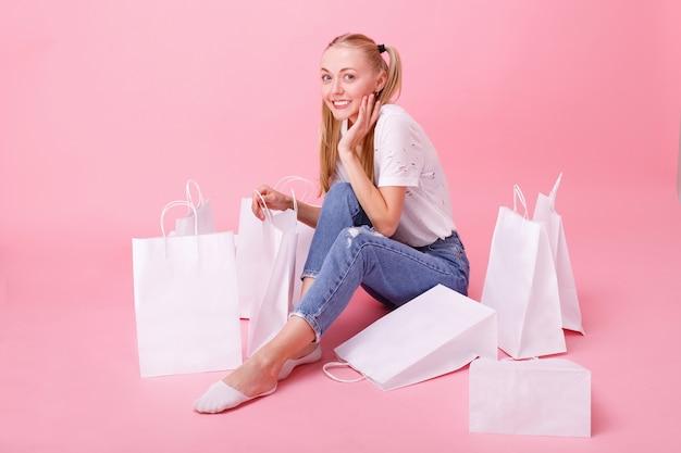 Meisje in een wit t-shirt met winkelen op roze