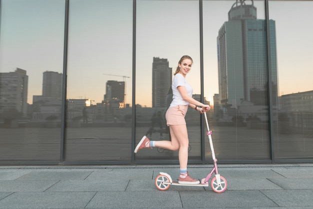Meisje in een wit t-shirt rijdt op een scooter tegen de achtergrond van een donkere muur, kijkt naar de camera en glimlacht.