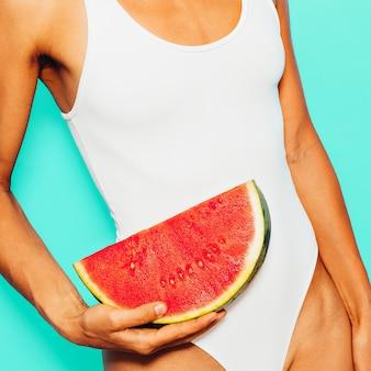 Meisje in een wit zwempak met watermeloen. frisse zomertrend