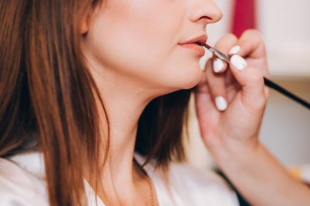 Meisje in een witte jas trekt lippen. meisje in de witte jas lacht. mooi meisje lachend. schilder je lippen met een penseel.