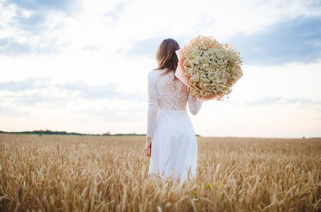 Meisje in een witte jurk bij zonsondergang