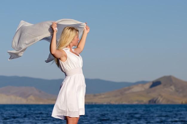 Meisje in een witte jurk en sjaal