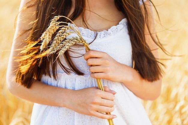 Meisje in een witte jurk houdt rijpe korenaren in haar handen