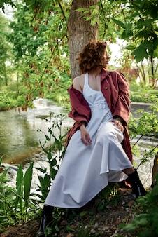 Meisje in een witte jurk in de buurt van de rivier