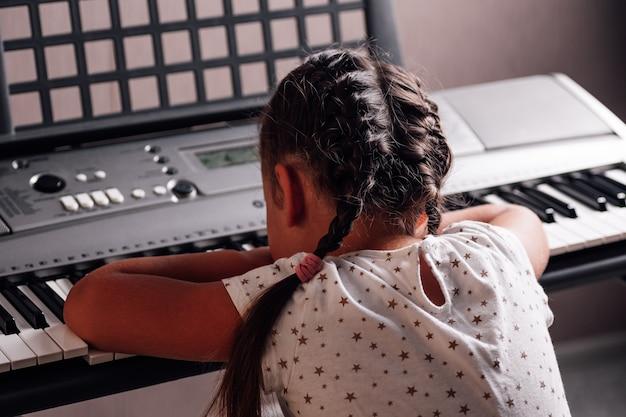 Meisje in een witte jurk ligt met haar hoofd op de toetsen van een elektronische synthesizer