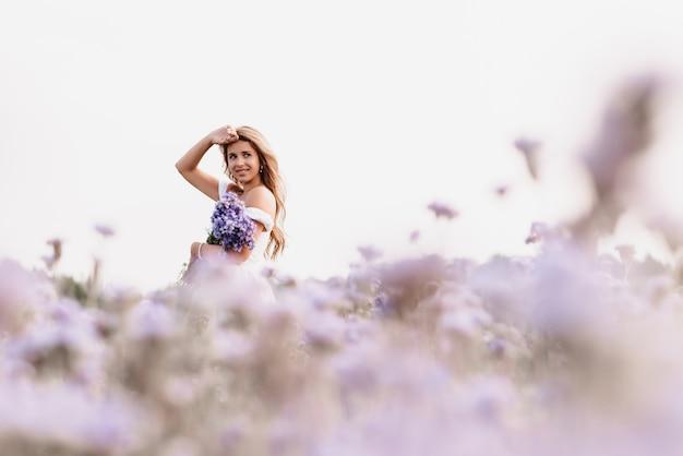Meisje in een witte jurk met een boeket paarse bloemen in een veld in de natuur in de zomer