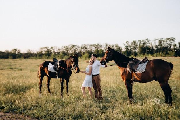 Meisje in een witte zomerjurk en een man in een wit overhemd op een wandeling met bruine paarden in het dorp
