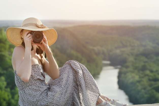 Meisje in een zomerjurk en een hoed met een camera. groen bos en rivier in de verte