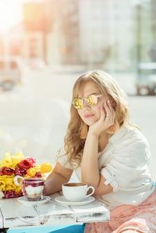 Meisje in een zomerterras met yoghurt en koffie