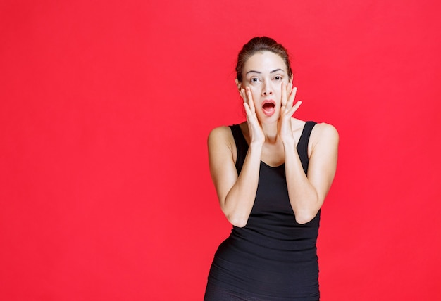 Meisje in een zwart shirt dat haar hoofd vasthoudt en als een dwaas reageert. hoge kwaliteit foto