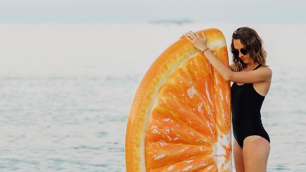 Meisje in een zwart zwempak met een oranje opblaasbare dobber op het strand Premium Foto