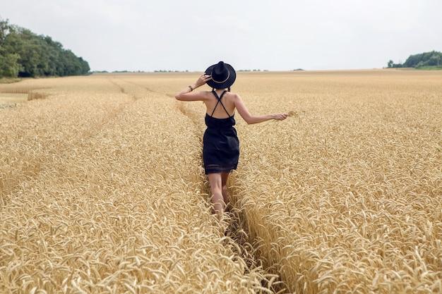 Meisje in een zwarte jurk en een hoed loopt