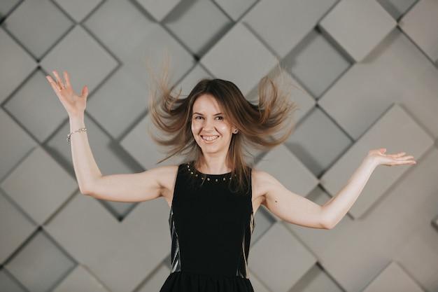 Meisje in een zwarte jurk speelt met haar haren en poses