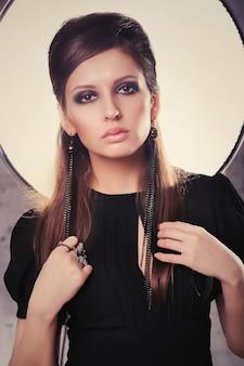 Meisje in een zwarte jurk staat in de studio