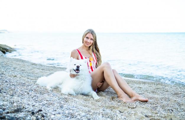 Meisje in een zwembroek met een hond op het strand, een hondenras samojeed