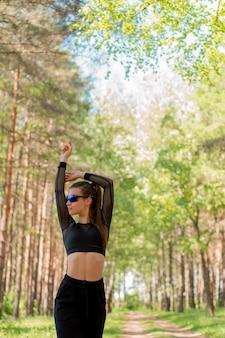 Meisje in eenvormig en zonnebril die sporten in een park doen