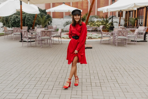 Meisje in elegante, rode jurk met riem en schoenen op stadshak toont slanke benen. foto van volledige lengte in stadscafé