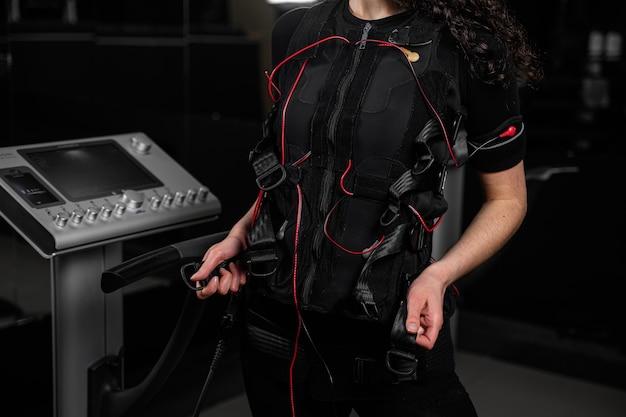 Meisje in ems-pak in de sportschool. sporttraining in elektrisch spierstimulatiepak. fysieke oefeningen maken.