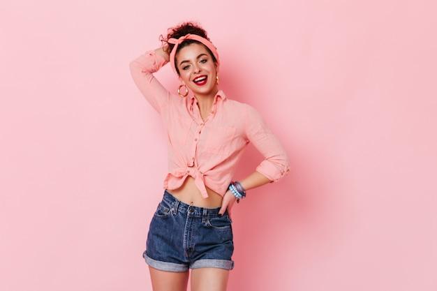 Meisje in enorme oorbellen, roze shirt en denim shorts poseren op roze ruimte met opgeheven arm.