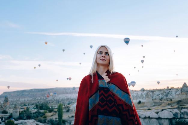 Meisje in etnische kleding bij dageraad kijken naar de vlucht veel ballonnen vliegen over de vallei van de liefde