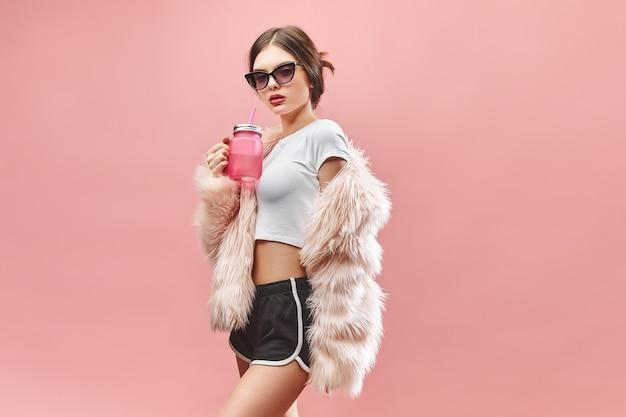 Meisje in faux roze bontjas zwarte korte broek witte top en zonnebril houdt roze drank vast met gesloten oog...