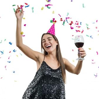 Meisje in feestmuts met glas rode wijn dansen onder confetti
