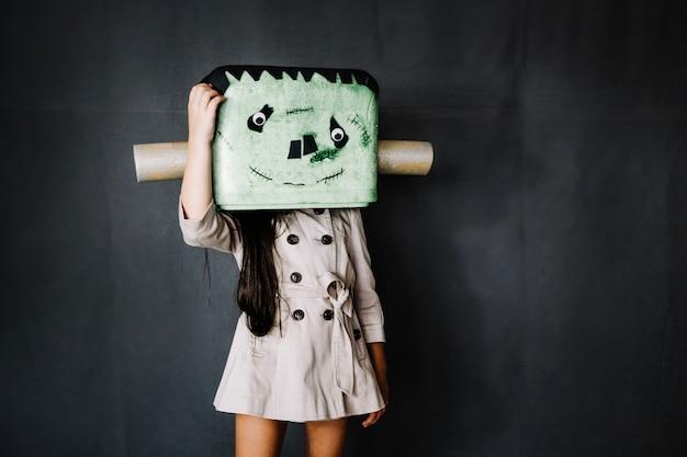 Meisje in frankenstein-masker knippert haar hoofd
