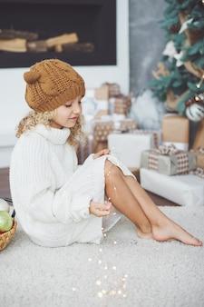 Meisje in gebreide muts in de buurt van de kerstboom doet een wens voor het nieuwe jaar.