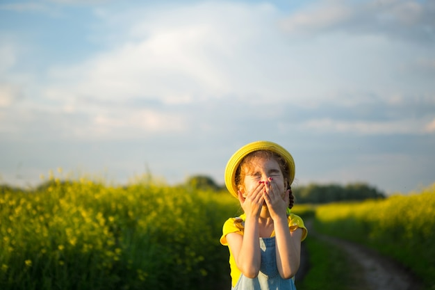 Meisje in geel bloeiend veld bedekte haar neus en gezicht met handen en gerimpeld - een onaangename geur, irritatie, allergie. allergische reactie op bloei in lente en zomer, muggenspray