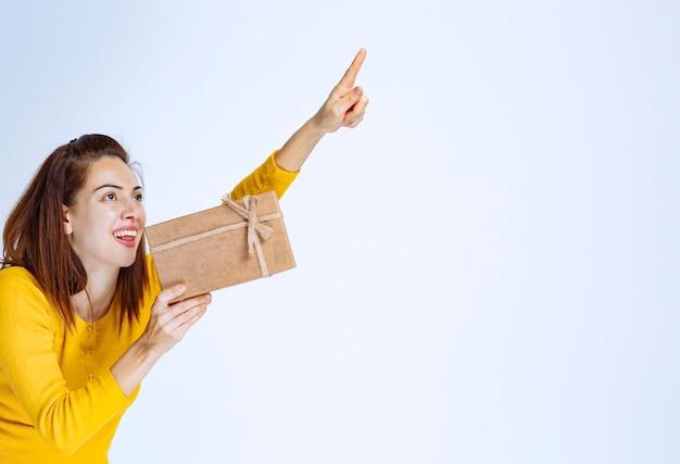 Meisje in geel overhemd met een kartonnen geschenkdoos en op zoek naar iemand om het te presenteren. Premium Foto