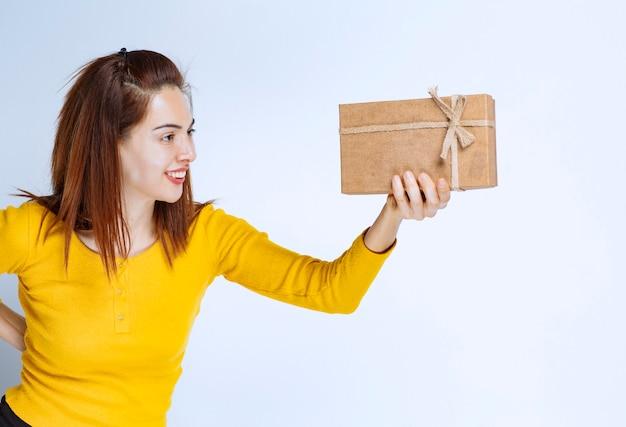 Meisje in geel overhemd met een kartonnen geschenkdoos.