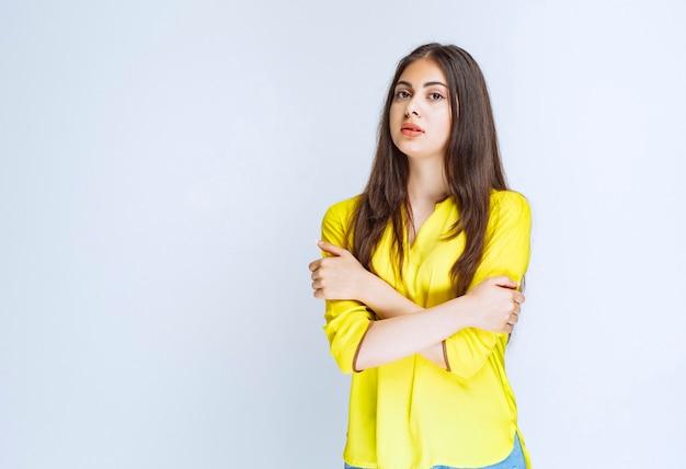 Meisje in geel shirt dat armen kruist en professionele poses geeft.