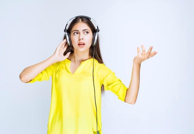 Meisje in geel shirt dat een koptelefoon draagt en er verward en doodsbang uitziet.