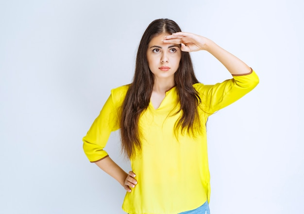 Meisje in geel shirt hand op haar voorhoofd en observeren of op zoek naar iemand.