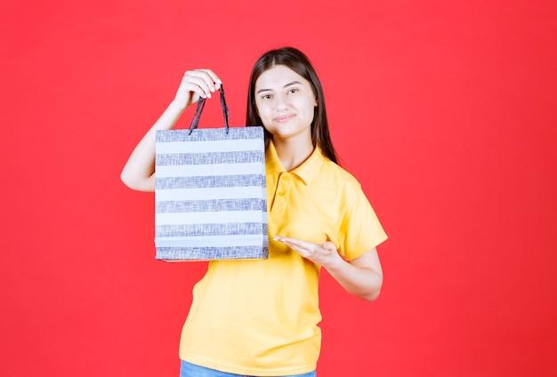 Meisje in geel shirt met een blauwe boodschappentas met patronen erop