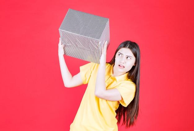 Meisje in geel shirt met zilveren geschenkdoos en ziet er bang en doodsbang uit.