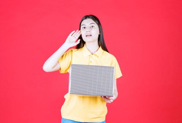 Meisje in geel shirt met zilveren geschenkdoos en ziet er verward en attent uit