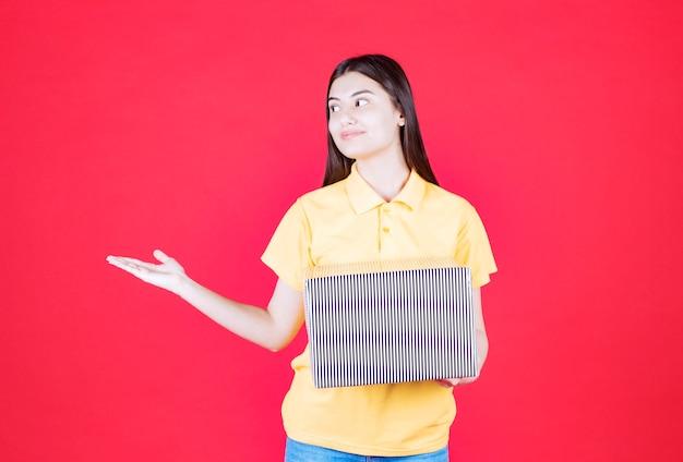 Meisje in geel shirt met zilveren geschenkdoos
