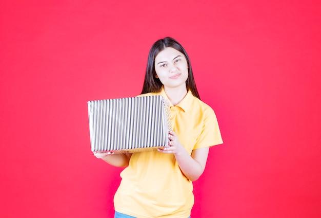 Meisje in geel shirt met zilveren geschenkdoos.