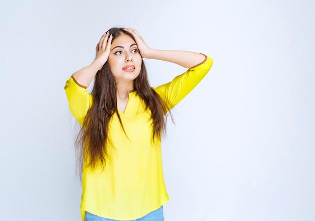 Meisje in geel shirt ziet er verward en twijfelachtig uit.