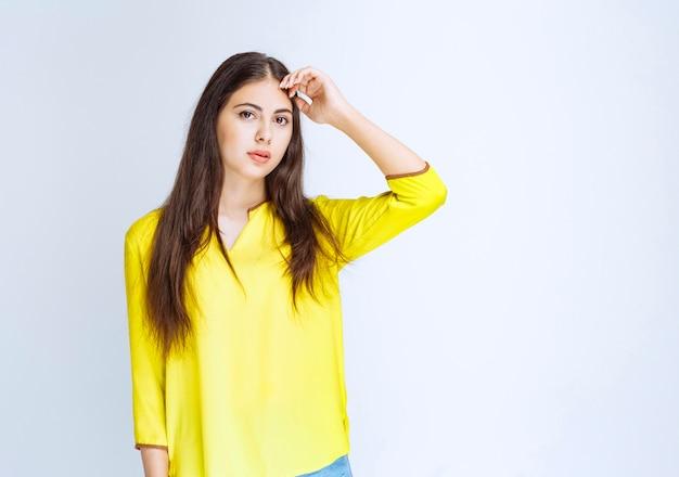 Meisje in geel shirt ziet er verward en verloren uit.