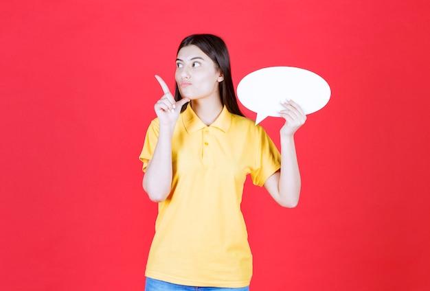 Meisje in gele dresscode met een ovaal infobord en kijkt bedachtzaam en aarzelend.