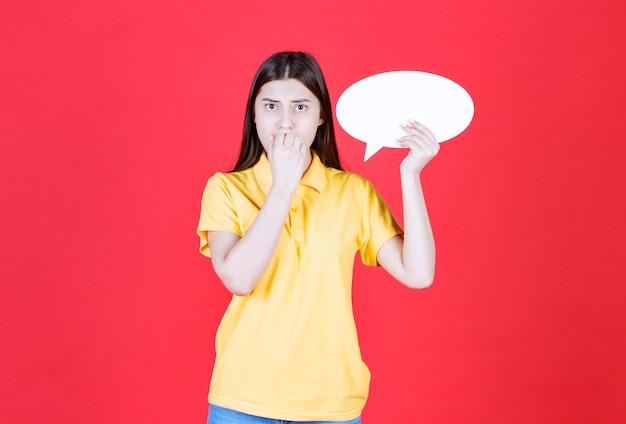 Meisje in gele dresscode met een ovaal infobord en kijkt doodsbang en gestrest.